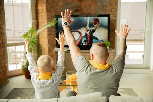 Família animada assistindo a um jogo de campeonato de basquete em casa pai e filho assistindo