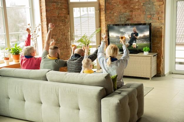Família animada assistindo a um jogo do campeonato de futebol americano em casa