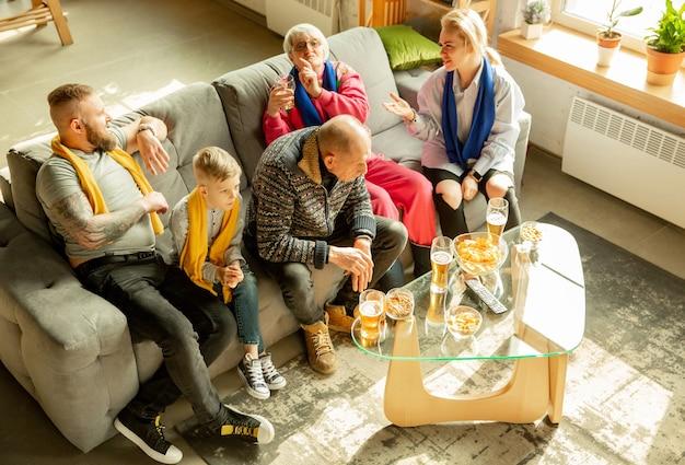 Família animada assistindo futebol, jogo de esporte em casa. avós, pais e filhos torcendo pelo basquete, futebol, tênis, futebol, time de hóquei nacional favorito. conceito de emoções, suporte.