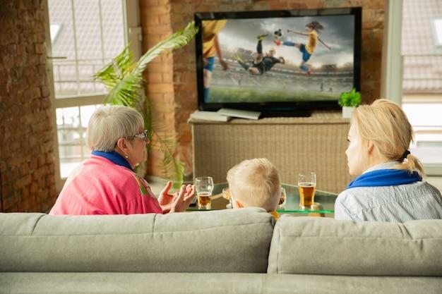 Família animada assistindo futebol, jogo de esporte em casa. vovó, mãe e filho torcendo pela seleção feminina de futebol com tradução. se divertindo. conceito de emoções, apoio, torcida.