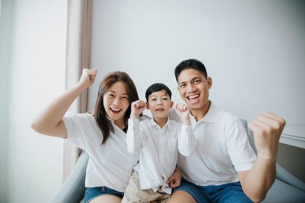 Família animada e feliz com os braços levantados enquanto assistia televisão em casa