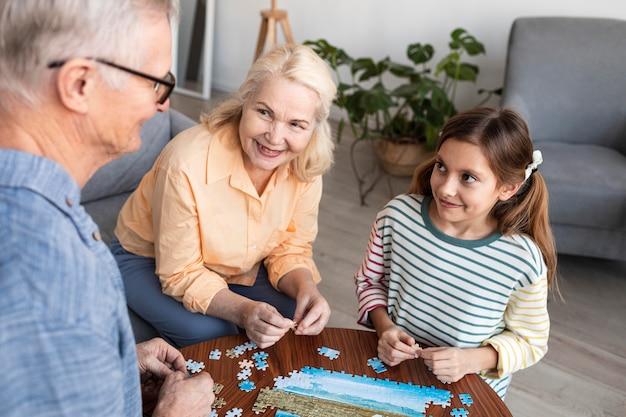 Família aproximada fazendo quebra-cabeças