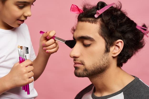 Família árabe. menina faz maquiagem para o pai.