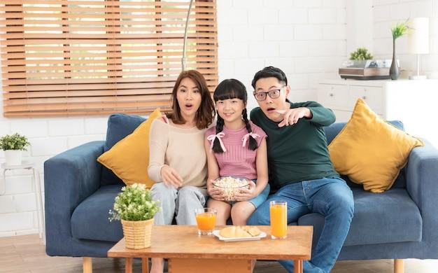 Família asiática animada comendo pipoca e assistindo tv no sofá na sala de casa