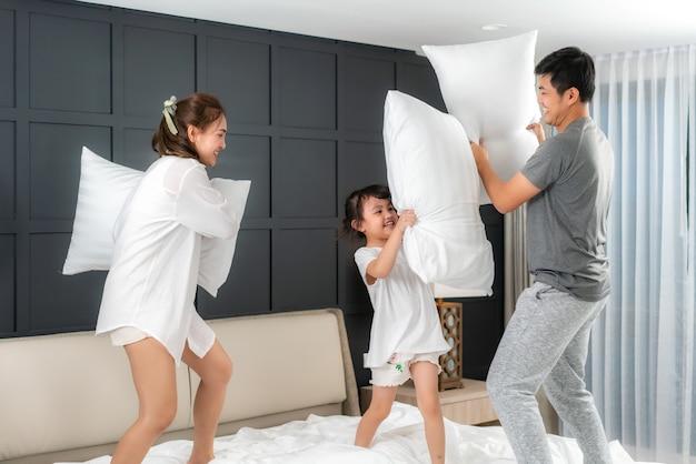 Família asiática brigando com travesseiros