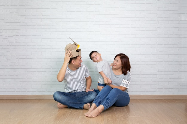 Família asiática brincando com o filho e sorrindo enquanto passa o tempo livre em casa
