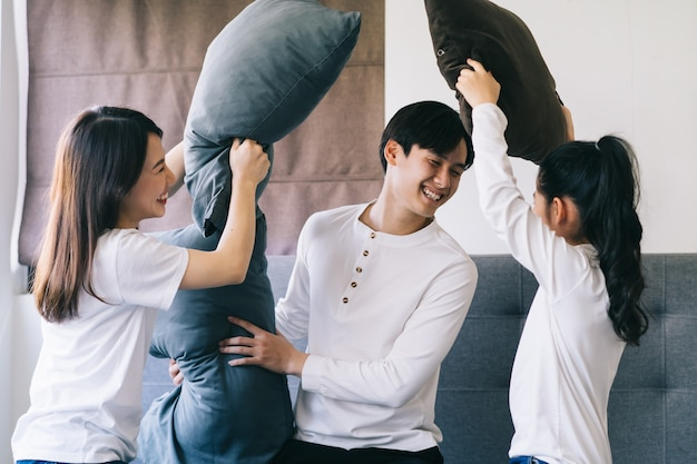 Família asiática brincando na cama