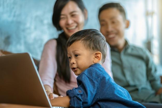 Família asiática, com, filho, é, olhar, a, caricatura, através, tecnologia, laptop, e, jogando junto