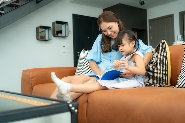 Família asiática com mãe e filha lendo livro de conto de fadas no sofá em casa