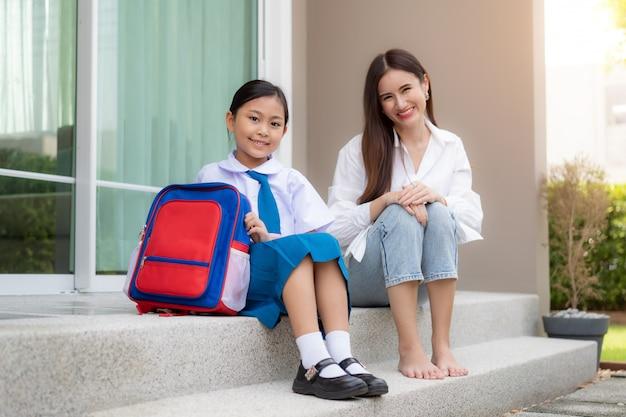 Família asiática com mãe e filha sentada e sorrindo em frente à casa para prepará-las para crianças do jardim de infância que colocam seu uniforme escolar com uma mochila e vão para a escola de manhã.