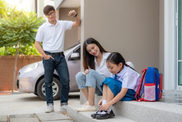 Família asiática com pai, mãe assistindo sua filha pré-escolares de uniforme para usar seus próprios sapatos