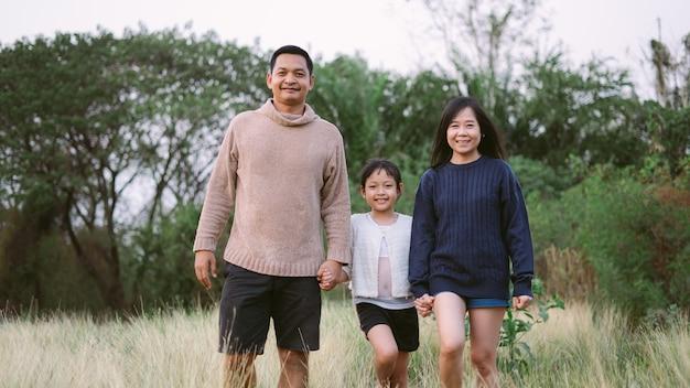 Família asiática com pai mãe e filha ter andando no parque com sorrindo e feliz