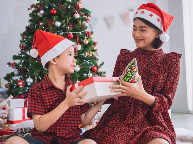 Família asiática comemorando o natal em casa com caixa de presente e árvore de natal