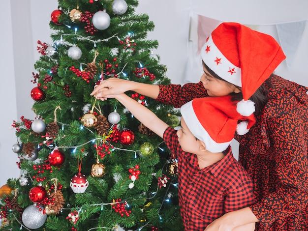 Família asiática comemorando o natal em casa, mãe e filho decoram a árvore de natal