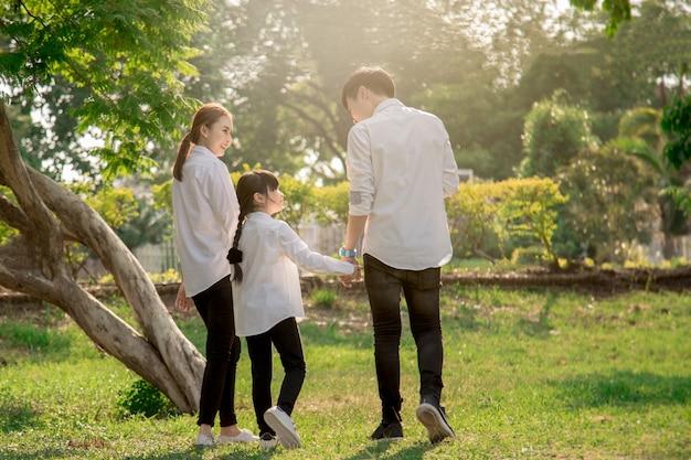 Família asiática da casa e filhos apontando para a casa
