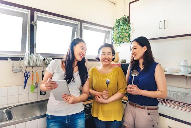 Família asiática de pé juntos na cozinha
