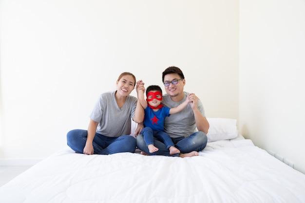 Família asiática e filho vestindo terno de super-herói mão e sentado na cama branca no quarto