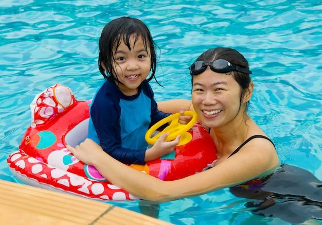 Família asiática, em, tubo nadar, tocando, ligado, piscina