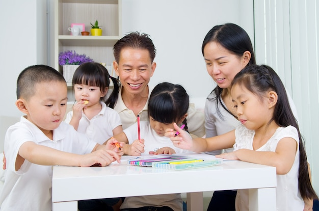 Família asiática fazendo lição de casa da escola na sala de estar
