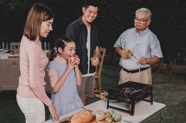 Família asiática fazendo um churrasco em casa. cozinhando churrasco grelhado para o jantar no quintal. estilo de vida nas férias de verão.