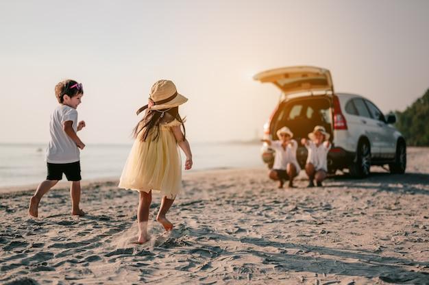 Família asiática feliz aproveitando a viagem à praia com seu carro favorito. pais e filhos estão viajando