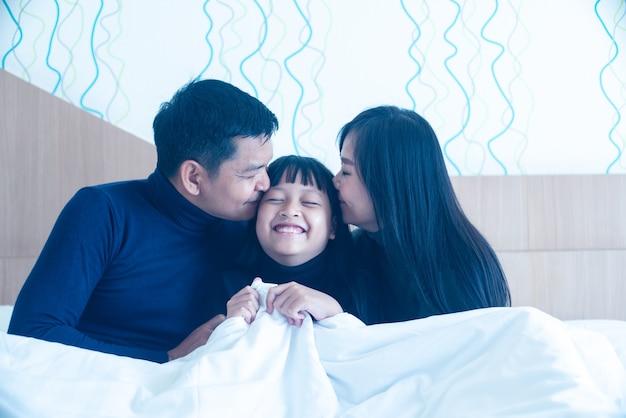 Família asiática feliz beijando filha em quarto de hotel