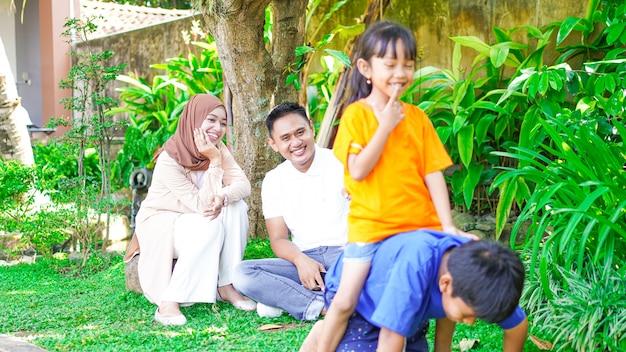 Família asiática feliz brincando no parque