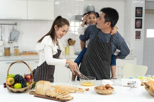 Família asiática feliz com a filha fazendo massa e preparando biscoitos, filha ajuda os pais a preparar o bolo conceito de família
