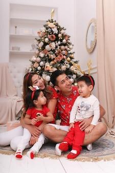 Família asiática feliz com dois filhos em pijamas vermelhos de natal se divertindo e rindo perto da árvore