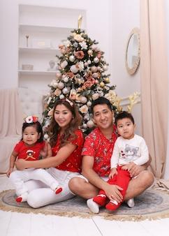 Família asiática feliz com dois filhos em pijamas vermelhos de natal se divertindo e rindo
