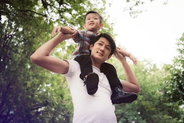 Família asiática feliz desfrutando de tempo para a família juntos no parque. conceito familiar