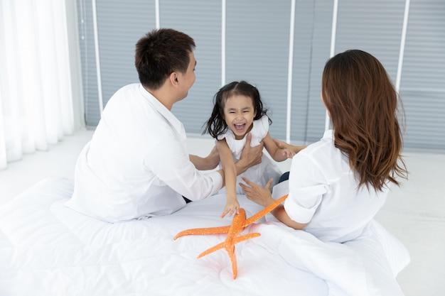Família asiática feliz em casa. atividades de lazer em família