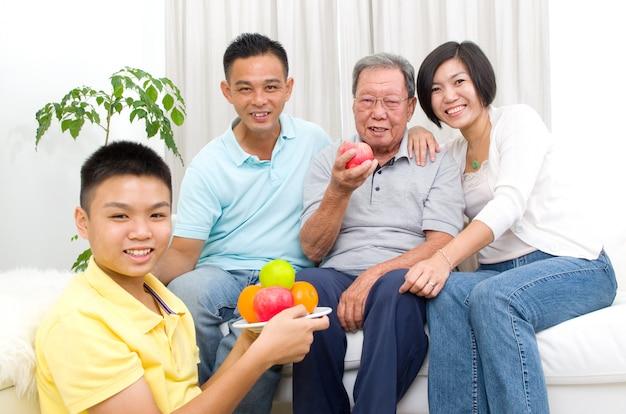 Família asiática feliz que come a fruta saudável.