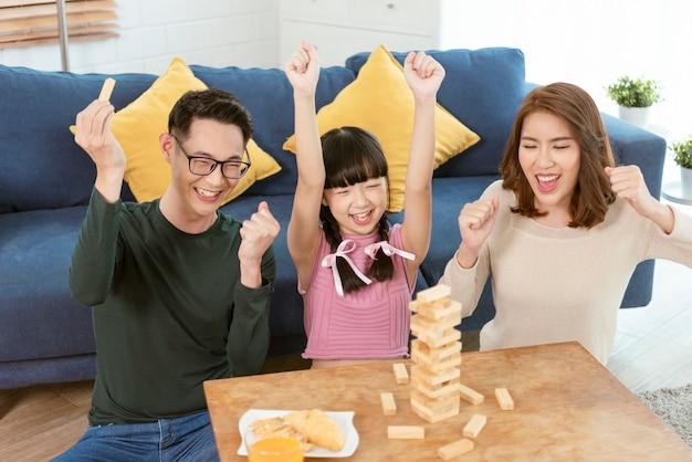 Família asiática feliz se divertindo jogando o jogo jenga na sala de estar em casa.