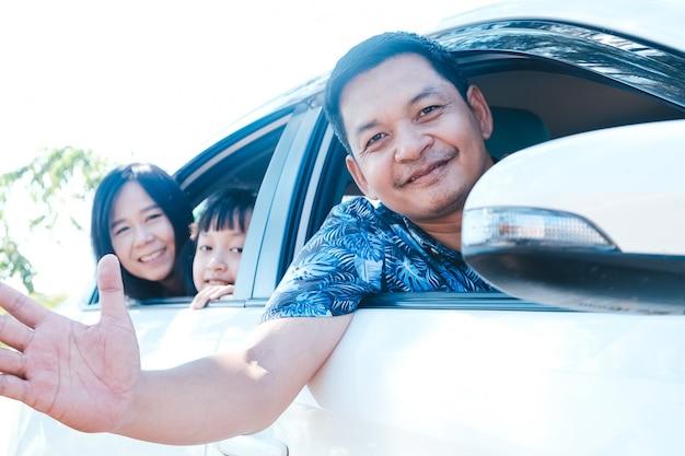 Família asiática feliz sentada no carro olhando pela janela