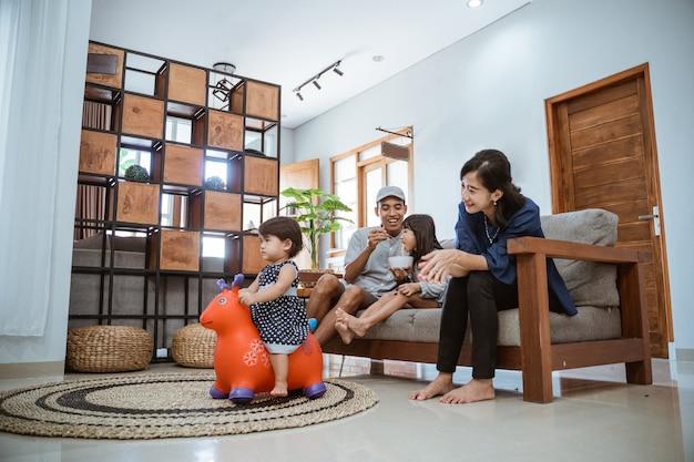 Família asiática feliz sentada no sofá em casa assistindo tv juntos