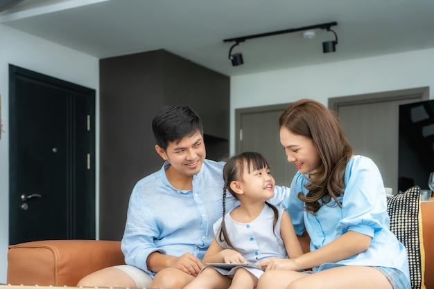 Família asiática feliz sentada no sofá