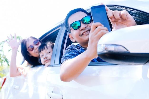 Família asiática feliz tirando uma selfie no carro