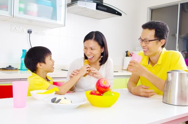 Família asiática feliz tomando café na cozinha