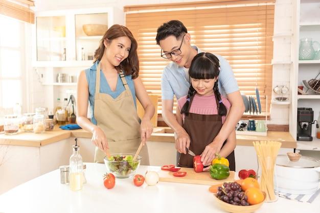 Família asiática gosta de cozinhar salada juntos na sala da cozinha em casa.