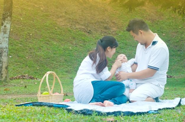 Família asiática jovem feliz, passar o tempo ao ar livre num dia de verão