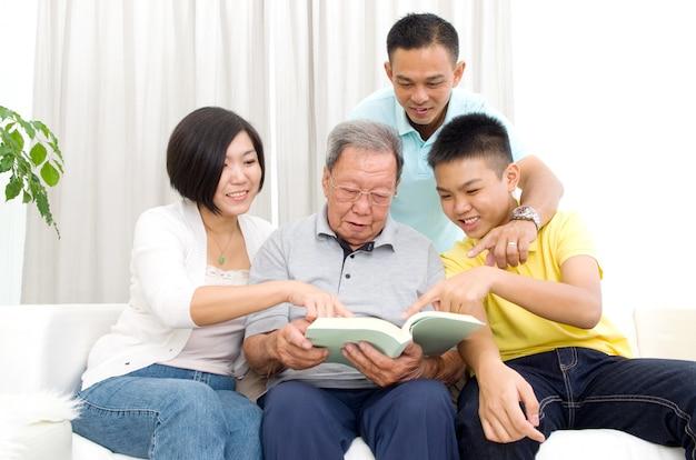 Família asiática, livro leitura, casa