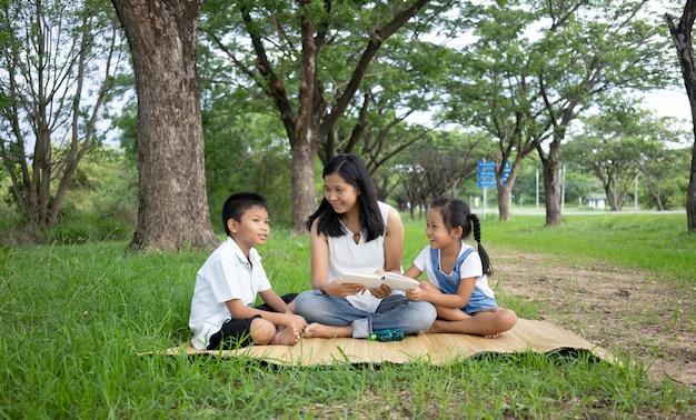 Família asiática, mãe, filho e filha fazendo atividades de leitura no parque