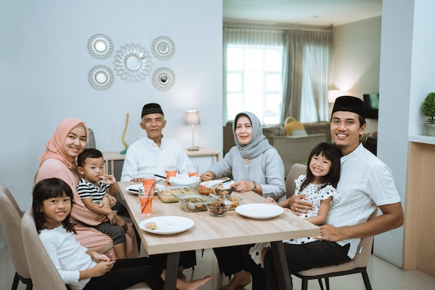 Família asiática muçulmana e avós, tendo o jejum de pausa no ramadã. intervalo para jantar iftar