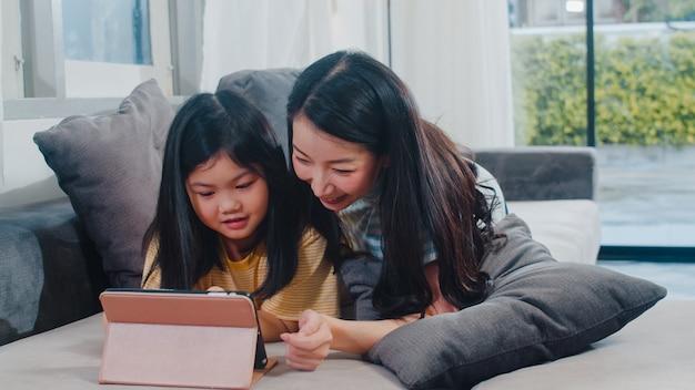 Família asiática nova e filha felizes usando a tabuleta em casa. mãe japonesa relaxar com a menina assistindo filme deitado no sofá na sala de estar em casa. mãe engraçada e criança adorável estão se divertindo.