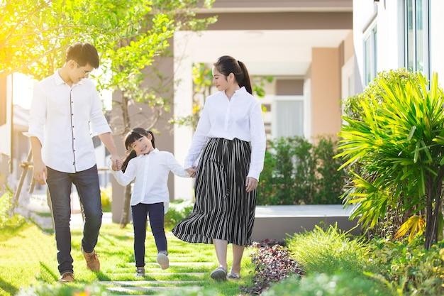 Família asiática os pais e as crianças estavam andando de mãos dadas juntos um feliz no jardim.