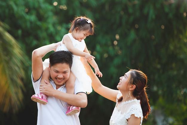 Família asiática pai mãe e filha brincando juntos no parque com amor e felicidade