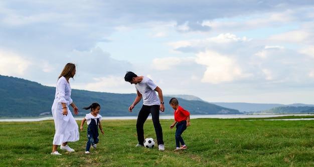 Família asiática pai, mãe e filha, filho, correr e jogar futebol no gramado
