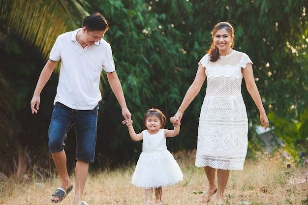 Família asiática pai mãe e filha segurando a mão e caminhando juntos no parque