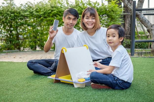 Família asiática, pai, mãe e filho brincando com um quadro-negro em uma horta
